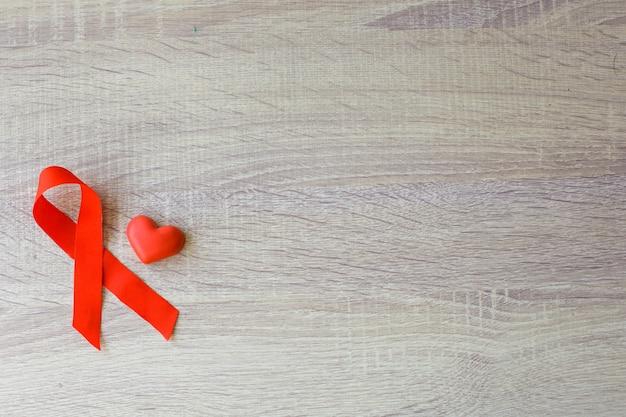 Красная лента вич спид и форма сердца для символа крови на деревянном фоне всемирный день борьбы со спидом