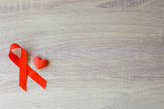 Red ribbon hiv aids and heart shape for blood symbol on wooden background world aids day