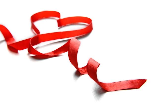 明るいテクスチャ背景にハートの形をした赤いリボン