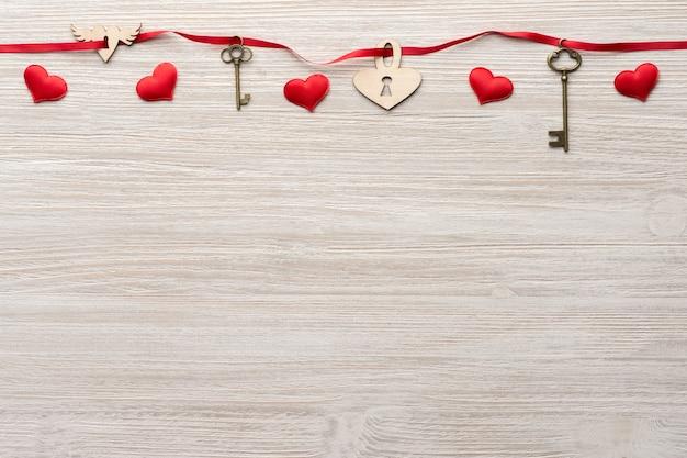 빨간 리본은 발렌타인 데이를위한 나무 배경에 두 개의 빈티지 키와 심장 잠금 장치를 통과합니다.
