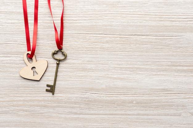 빨간 리본은 발렌타인 데이를위한 나무 배경에 빈티지 키와 심장 잠금 장치를 통과합니다.