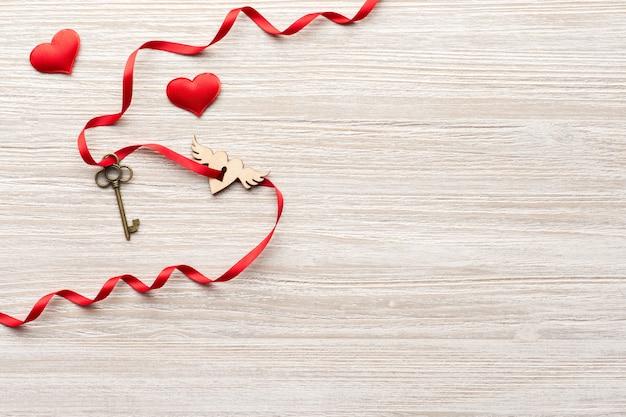 Красная лента проходит через старинный ключ и замок-сердце на деревянном фоне на день святого валентина