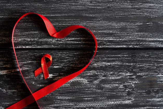 Red ribbon in shape of heart awareness on black wooden table background. world aids day ca
