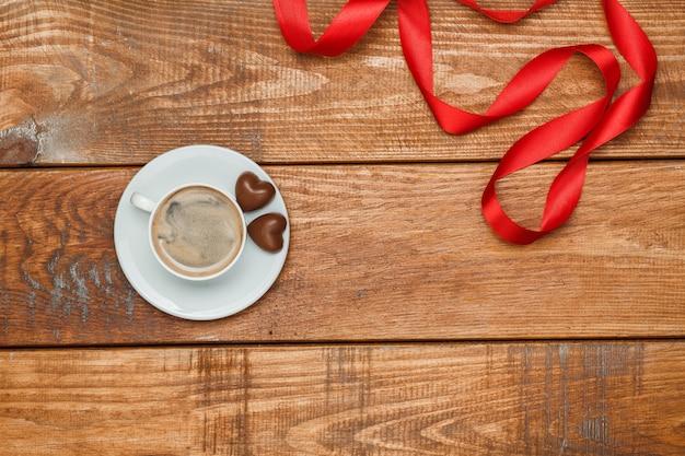 Il nastro rosso, piccoli cuori su legno con una tazza di caffè