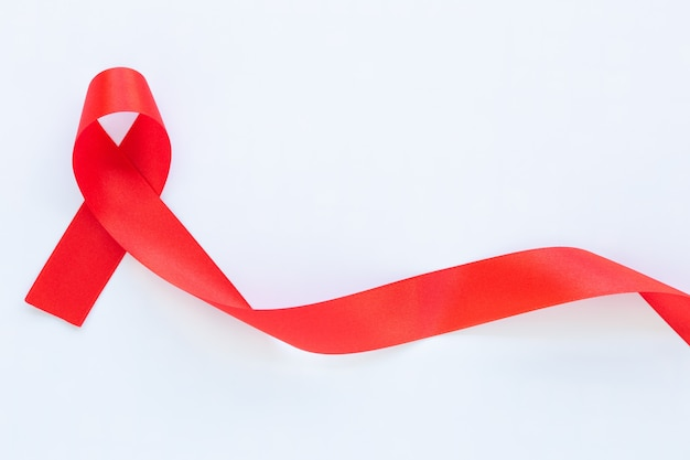 Red ribbon on white fabric table with copy space symbol for the solidarity of people living with hivaids and for the awareness and prevention of drug abuse and drunk driving health concept