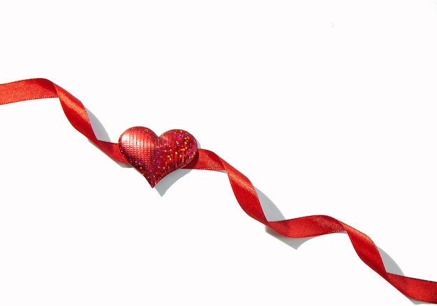 Red ribbon with shiny red heart isolated on white background