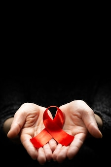 Red ribbon in woman hands on dark surface for world aids day concept