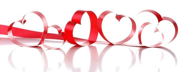 Красные ленты в форме сердечек, изолированные на белом фоне