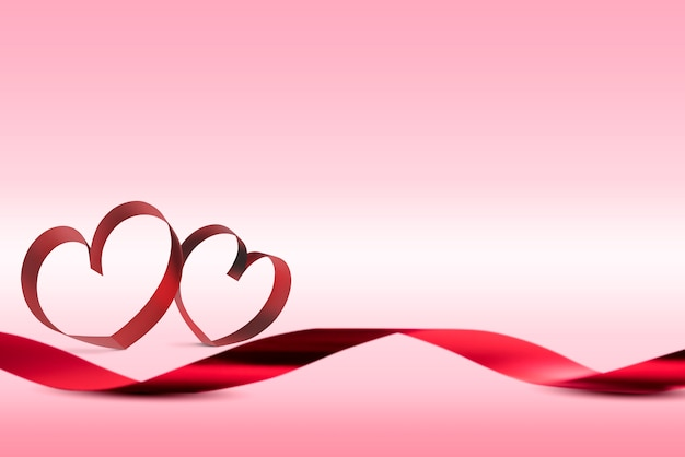Red ribbons with ribbons shaped as hearts over pink background