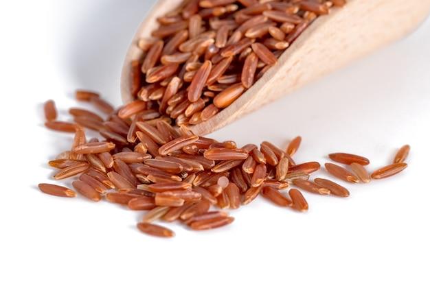 白い健康食品に分離された木のスプーンの赤いご飯