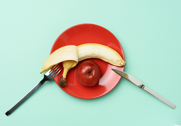 赤い熟したリンゴとバナナは、金属ナイフの近くの赤い丸いセラミックプレートに横たわっています