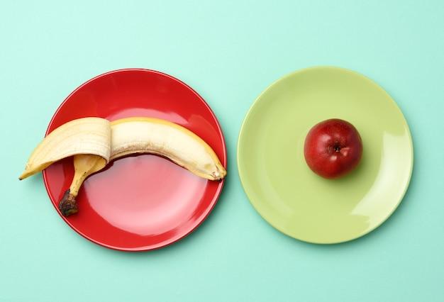 Красное спелое яблоко и банан лежат на круглой керамической тарелке