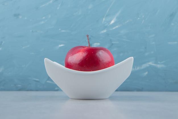 白いボウルに赤い熟したリンゴ