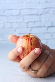 白で隔離され、女性の手に赤い熟したリンゴ。