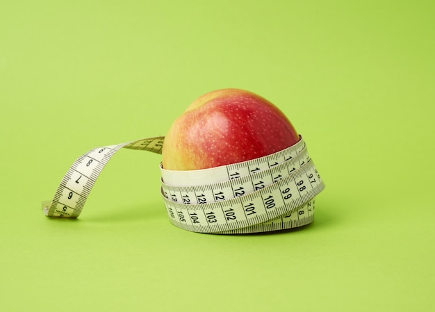 Red ripe apple wrapped with a centimeter on a green background, body weight control concept, weight loss