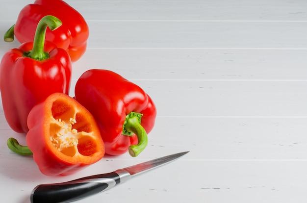 Красный спелый перец и кухонный нож. белый деревянный. копировать пространство