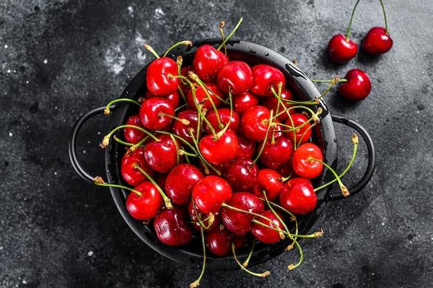 Красные спелые вишни на дуршлаге. черный фон. вид сверху.
