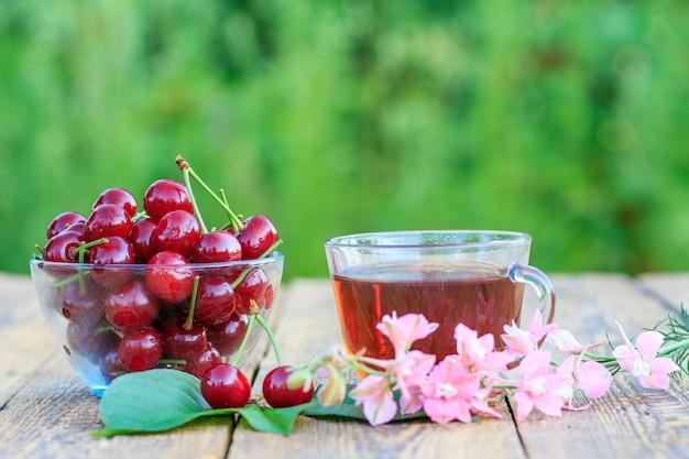 ガラスのボウルに茎があり、古い木の板にお茶が入った赤い熟したチェリーフルーツ。さくらんぼに選択的に焦点を当てる