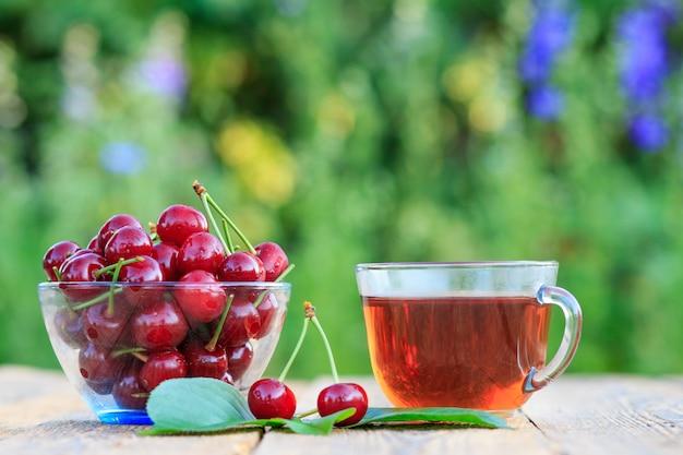 ガラスのボウルに茎と古い木の板にお茶を入れた赤い熟した桜の果実