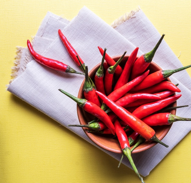 Red ripe chili peppers in a bowl over yellow surface