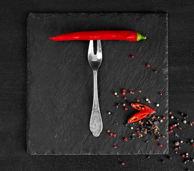フォークに赤唐辛子、黒い表面にドライスパイスのエンドウ豆。上面図