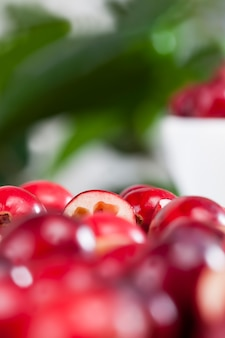 テーブルの上の赤く熟した分割クランベリー、赤カットの酸っぱい有用なクランベリー、スライスにカットされた工業用庭園で栽培された自家製クランベリー