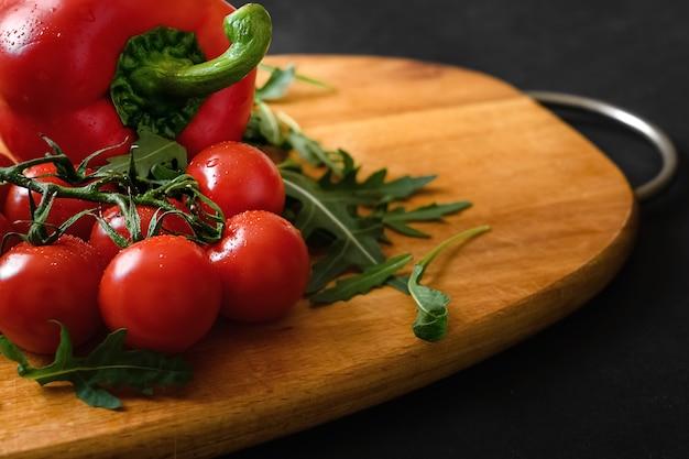 枝に赤く熟したフレッシュチェリートマト、木製のまな板にコショウと緑のルッコラ。健康的な食事とダイエット