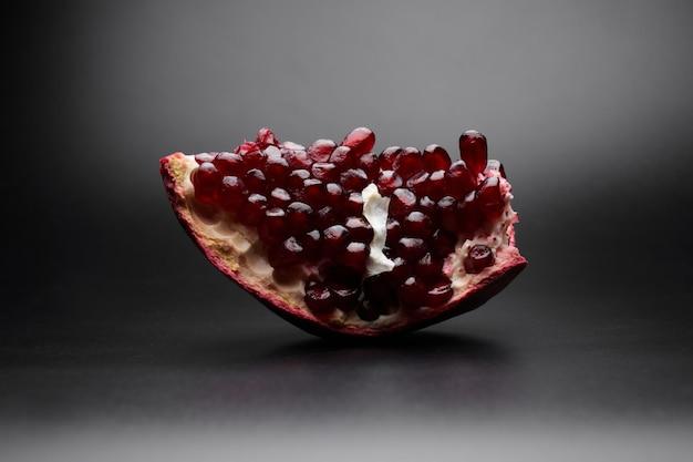 검은 배경에 고립 된 붉은 익은 신선한 육즙 얇게 썬 석류