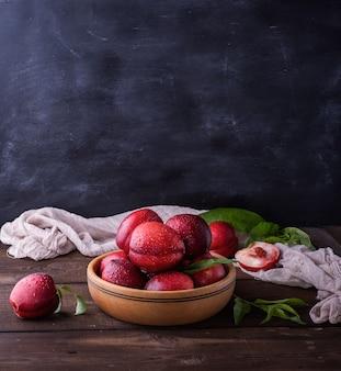 木の板に赤熟した桃のネクタリン、クローズアップ