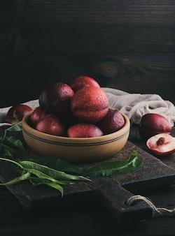木の板の赤い熟した桃のネクタリン、クローズアップ