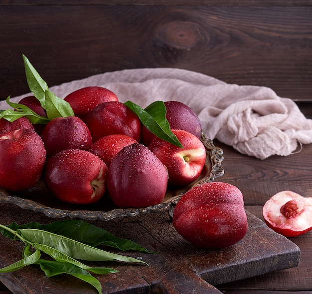 Red ripe peaches nectarine in an iron plate