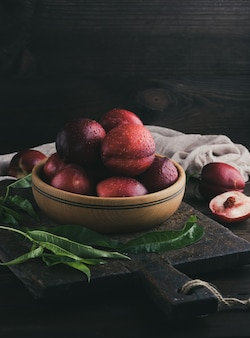 Red ripe peaches nectarine in a wooden plate, close up