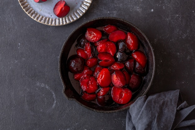 Red ripe plums caramelised in cast iron on dark background. top view