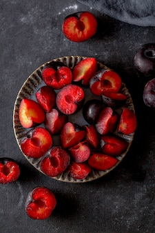Red ripe plums sliced on dark background. top view