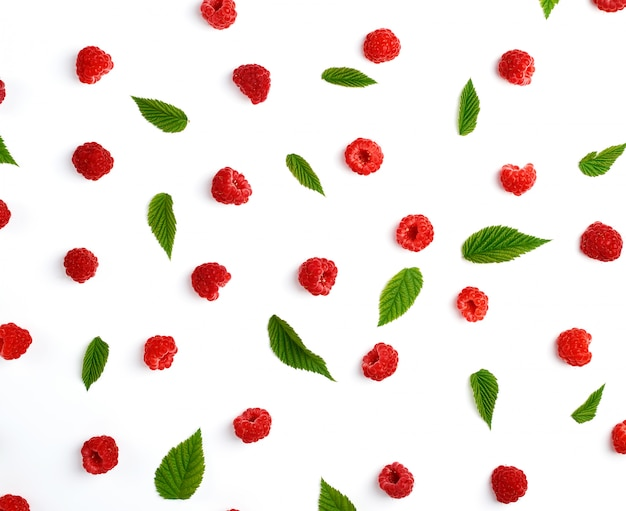 Red ripe raspberries and green leaves scattered on a white background