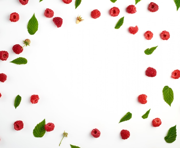 Red ripe raspberries and green leaves scattered on white