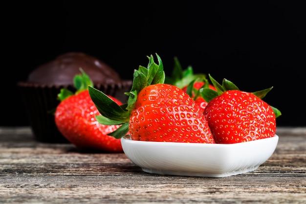 나무 테이블에 빨간색 잘 익은 딸기와 초콜릿 컵 케이크, 건강한 딸기의 근접 촬영, 동물성 성분이없는 컵 케이크, 채식 음식