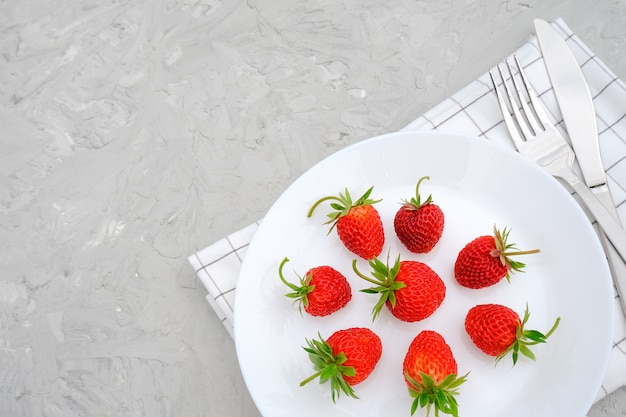 Red ripe strawberries berry on white plate, cutlery and red alarm clock on gray stone