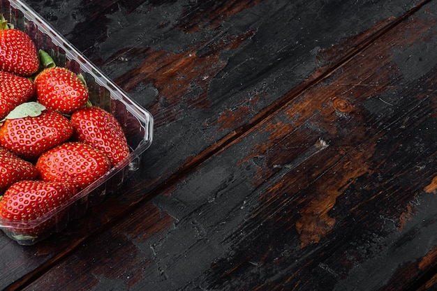 Red ripe strawberries in clear plastic tray, on old dark wooden table