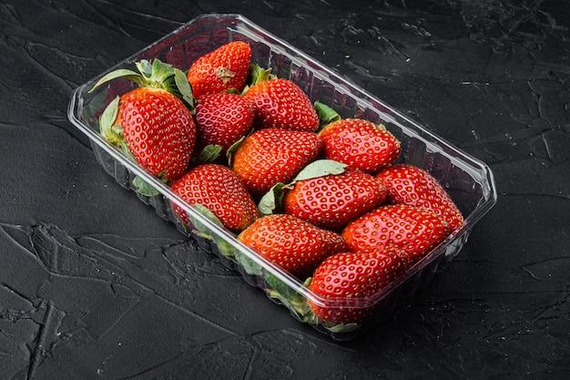 검은 바탕에 투명 플라스틱 트레이에 빨간색 잘 익은 딸기