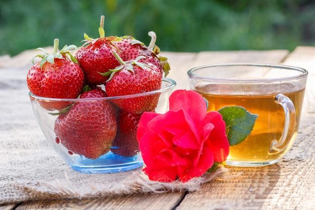 Красная спелая клубника в стеклянной миске и чашка зеленого чая с розовым цветком на вретище и старые деревянные доски с размытым естественным фоном