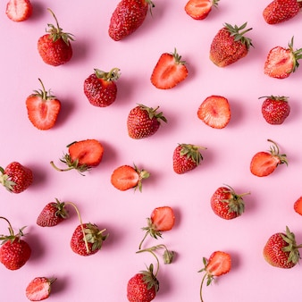Red ripe strawberries over pink, flat lay.
