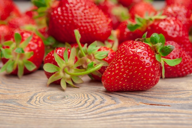 Red ripe strawberries on wooden table close up