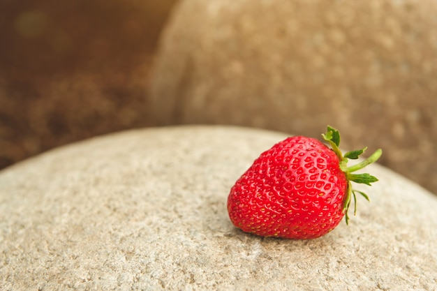 Red ripe strawberry on a stone