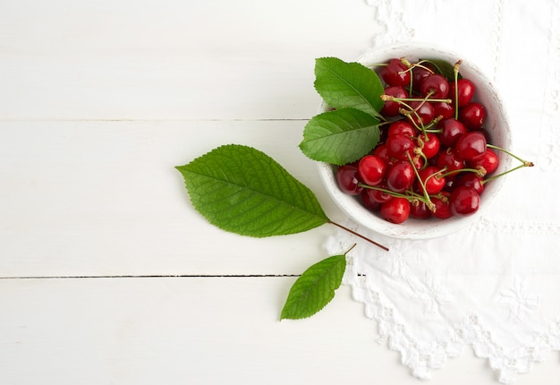 Red ripe sweet cherries in a round wooden plate on a white background, top view