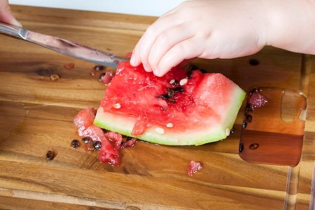 Красный спелый арбуз нарезать кусочками