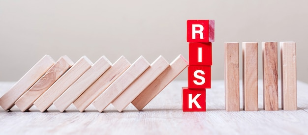 빨간색 위험 큐브 블록은 테이블에서 떨어지는 블록을 중지합니다. 가을 비즈니스, 계획, 관리, 솔루션, 보험 및 전략 개념