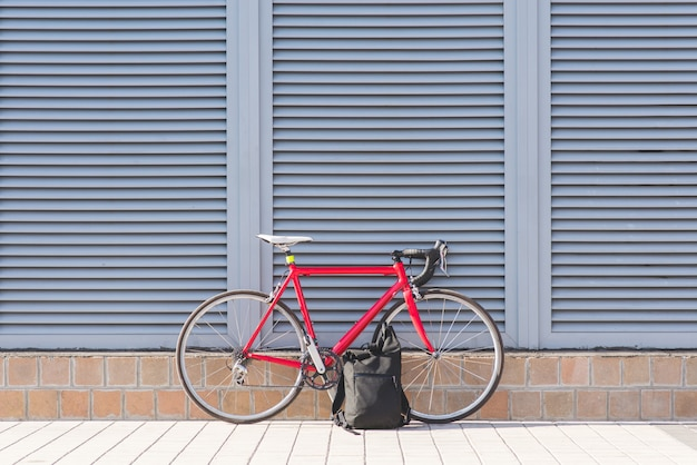 Red road bike and backpack against a gray wall