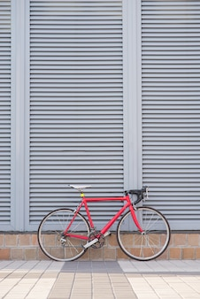 Red road bike stands on a gray wall