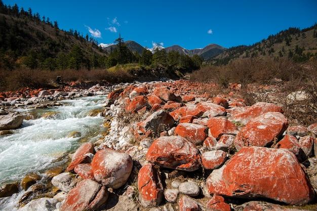 Красная скала на потоке и голубое небо